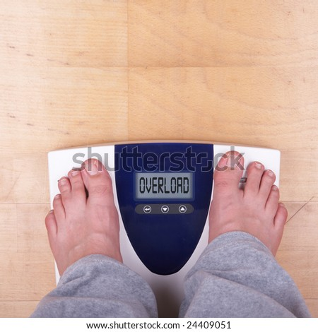 "A scale with two feet of the person standing on it on a wooden floor. The scale says: ""OVERLOAD"". - stock photo"