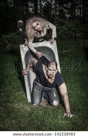 a scary and bloody zombie couple - stock photo