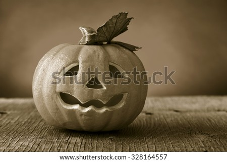 a scary carved pumpkin on a rustic wooden surface, in sepia toning, with a dramatic effect - stock photo