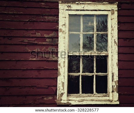A scary dark wooden window on a house with peeling red paint for a fear or danger crime concept. - stock photo