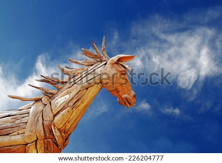 A scary gnarly wooden horse against a blue sky with wispy cloud.  - stock photo