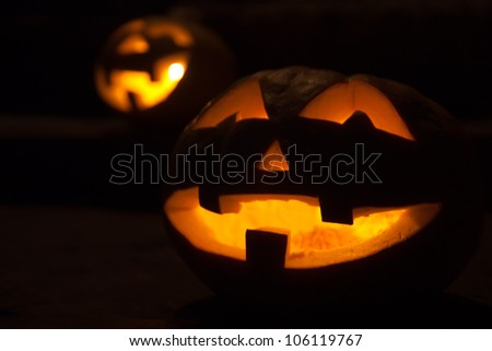 A scary old jack-o-lantern on black. - stock photo