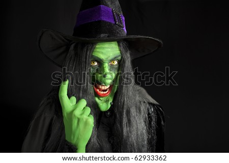 A scary witch, signaling come here. - stock photo