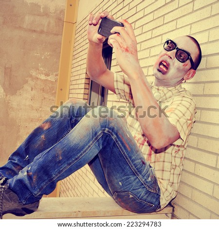 a scary zombie taking a selfie of himself with a smartphone, with a retro effect - stock photo