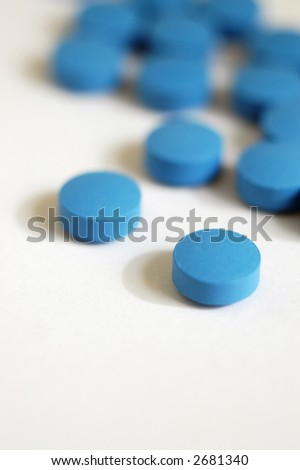 A scattering of blue pills of a psychiatric medication, vertical with copy space - stock photo