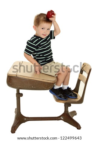 A school boy sits on a desk holding an apple on his head isolated on white - stock photo