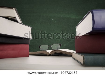 A school chalkboard and teacher's desk with stack of textbooks and glasses. Copy space on blackboard. - stock photo