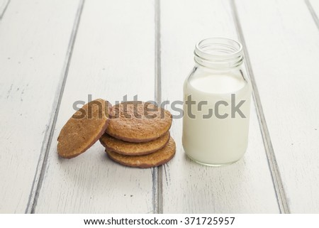 A school milk bottle and a heap of chocolate biscuits on a white wooden table - stock photo