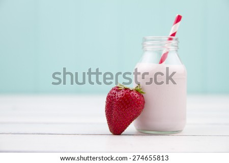 A school milk bottle with strawberry milkshake, a strawberry and a red and white straw on a white wooden table with a turquoise background - stock photo