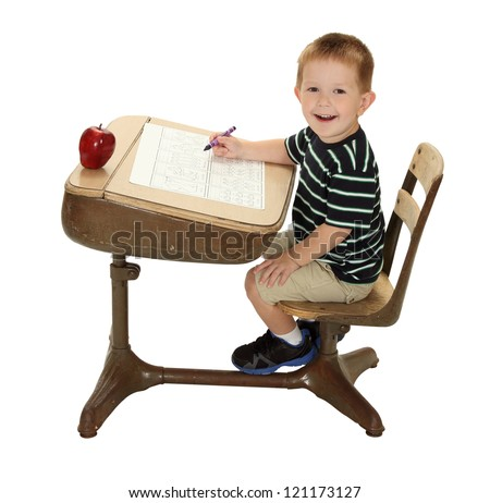 A school student is happy at his desk writing with a crayon and apple for the teacher - stock photo