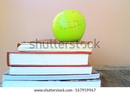 A school teacher's desk with stack of exercise books and apple . A blank blackboard in soft focus background provides copy space.  - stock photo