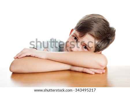 A schoolboy is laying his head on hands, isolated on white background - stock photo