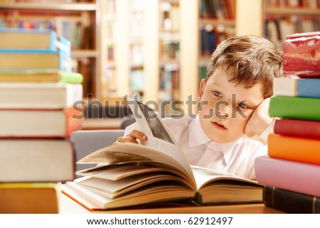 A schoolboy sitting in the library and turning the pages over - stock photo