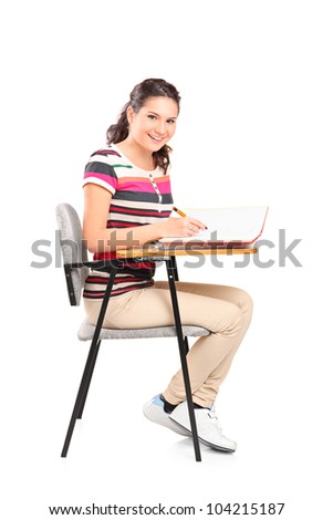 A schoolgirl sitting on a chair and writing down notes isolated on white background - stock photo