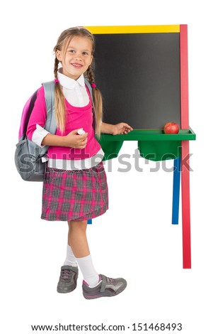A schoolgirl standing next to the blank blackboard, isolated - stock photo