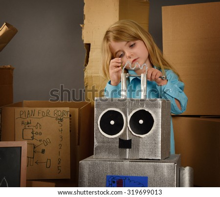 A science student is inventing a metal robot out of cardboard boxes with tools. Use it for an education or imagination concept. - stock photo