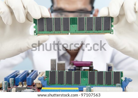 A scientist checking the memory card of motherboard - stock photo