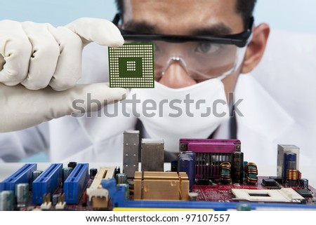 A scientist focusing at a chip of motherboard - stock photo