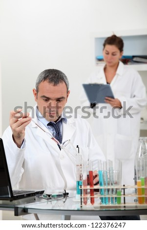 a scientist using test tubes - stock photo