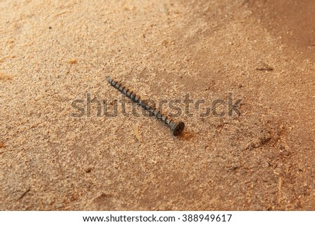 A screw on the dusty table,effective area. Furniture assembly. - stock photo