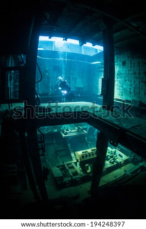 A scuba diver explores the inside of a shipwreck intentionally sunk as a diving and snorkeling attraction in Grand Cayman Island. Shipwrecks can serve as artificial reefs. - stock photo