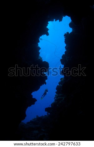 A scuba diver explores the mouth of an underwater cave off the Caribbean island of Grand Cayman. The Caymans are a popular vacation destination for divers, snorkelers, and beach lovers. - stock photo