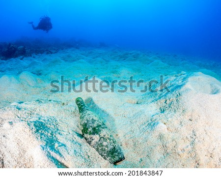 A SCUBA diver swims over a discarded bottle and sand on a destroyed,lifeless coral reef - stock photo