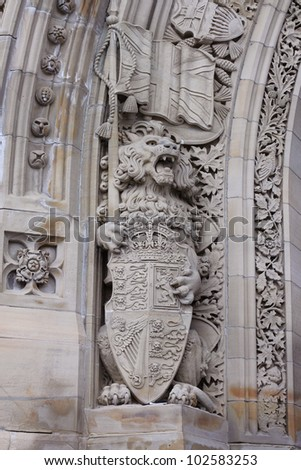 A sculpture of a lion holding the shield of Canada at the entrance of the Parliament buildings in Ottawa. - stock photo