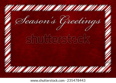 A Season's Greetings card, A Candy Cane border with words Season's Greetings over red plush background with copy-space - stock photo