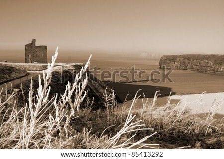 a seasonal snow covered view of atlantic ocean and ballybunion castle beach and cliffs on a frosty snow covered winters day in sepia - stock photo