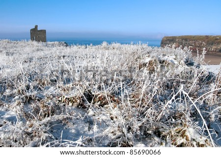 a seasonal snow covered view of atlantic ocean and ballybunion castle beach and cliffs on a frosty snow covered winters day - stock photo
