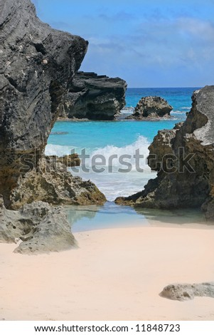 A secluded pink beach and turquoise ocean on the shoreline of Bermuda. - stock photo