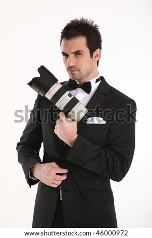 A secret agent with a telephoto lens in his hand, holding it like a gun, in tuxedo. - stock photo