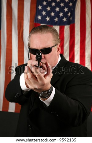 a Secret Service Agent points his weapon at YOU the Viewer - stock photo