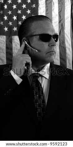a Secret Service Agent speaks on his ear piece in black and white - stock photo