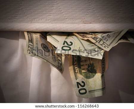 A secret stash of money is hiding under a mattress bed. - stock photo