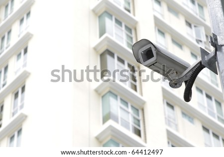 A security camera in front of an apartment block - stock photo