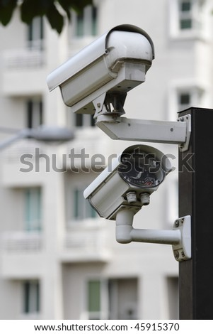 A security camera with LED light monitoring the compound of a residential building - stock photo