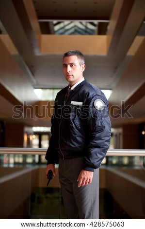 a security guard checking his area inside of a building with a portable wireless transceiver - stock photo