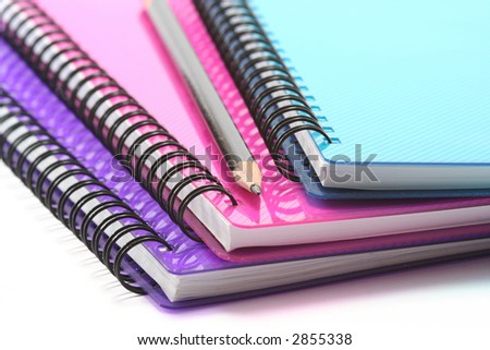 A selection of brightly coloured spiral bound notebooks with pencil - stock photo