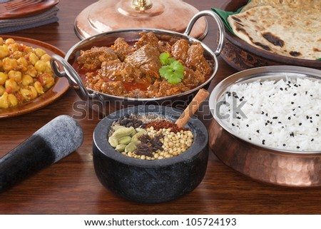 A selection of Indian food and spices, lamb rogan josh, chana masala, spices, basmati rice and parathas. The spices shown are the ones  used in the lamb curry. - stock photo