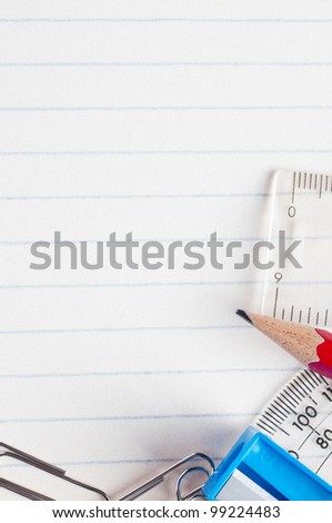 A selection of stationery bordering the bottom and right side of a lined paper background from a school exercise book. - stock photo
