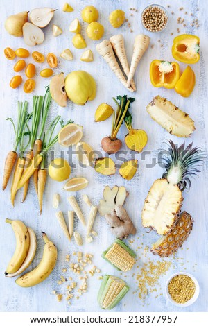 A selection of various fresh yellow raw organic produce fruits and vegetables pineapple carrot parsnip capsicum soy beans lemon tomato pear corn banana beetroot - part of a color spectrum collection - stock photo
