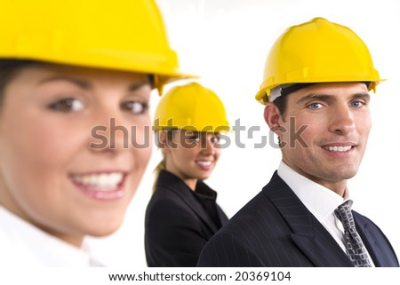 A selective focus industrial concept shot showing 2 women and a man dressed in hard hats. The focus is on the man on the right of the shot. - stock photo
