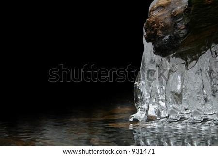 A semi-frozen river with icicles.  Left 2/3 black for add space or wallpaper for icons in PC. - stock photo