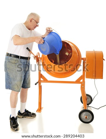 A senior adult man pouring sand into his cement mixer.  On a white background. - stock photo