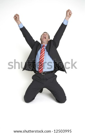 A senior businessman drops to his knees and throws his hands in the air in celebration. - stock photo
