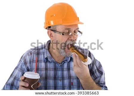 A senior caucasian man in orange helmet eats a cake and has a coffee - stock photo
