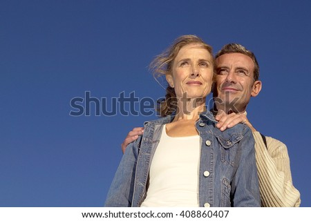 A senior couple, close together, looking at the horizon - stock photo