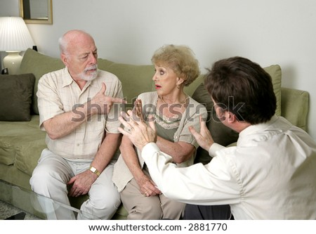 A senior couple in counseling argues as their therapist tries to calm then down. - stock photo